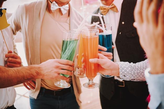 Óculos de tilintar alegre em gays com cocktails diferentes.
