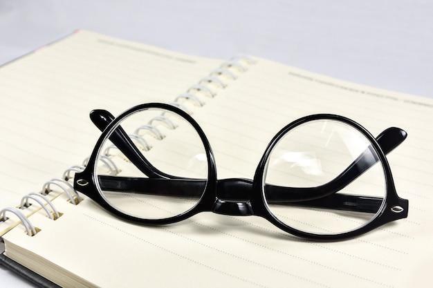 Óculos de trabalho e livros de leitura são colocados no livro.