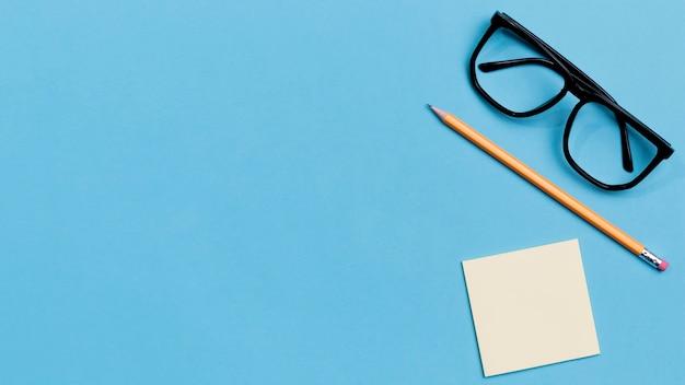 Óculos de vista superior e lápis com espaço de cópia