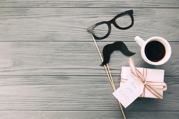 Óculos decorativos e bigode perto de presente com caneca de bebida
