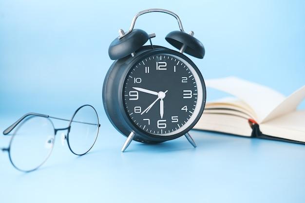 Óculos despertador e livro na mesa