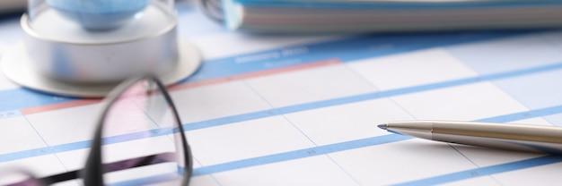 Óculos e ampulheta estão no calendário no escritório closeup. chegue a tempo pelo conceito de prazo