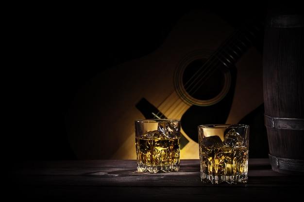 Óculos e barril de uísque na parede da guitarra