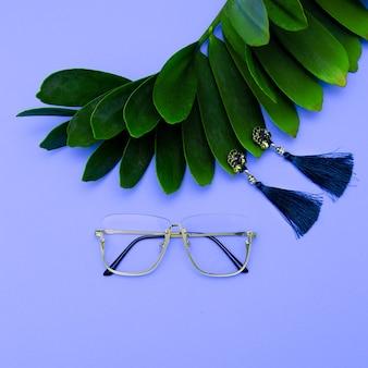 Óculos e brincos. acessórios elegantes para mulheres. postura plana