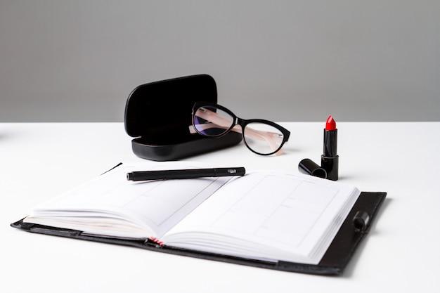 Óculos e caderno de batom vermelho sobre a superfície branca
