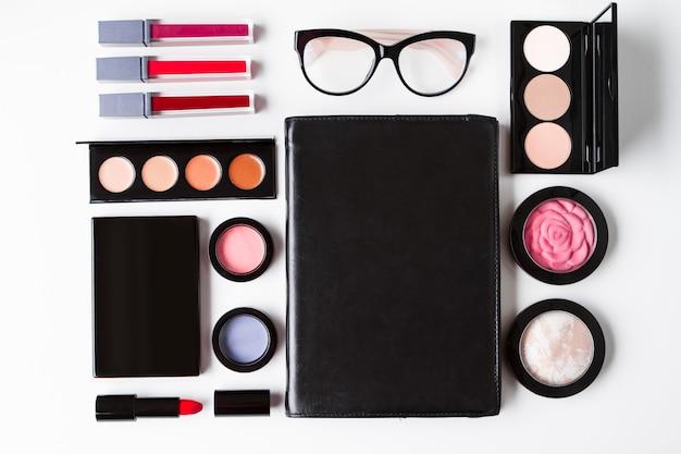 Óculos e caderno de cosméticos decorativos sobre fundo branco