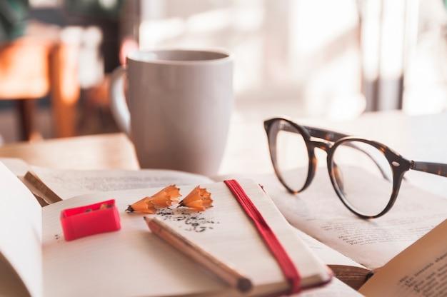 Óculos e caneca perto de caderno e livros