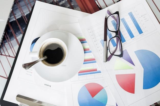 Óculos e caneta em papéis com diagramas coloridos na mesa