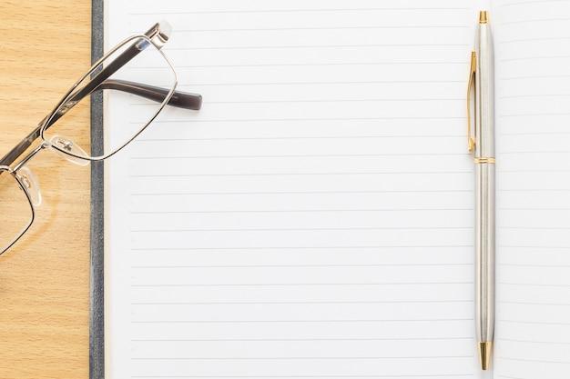 Óculos e caneta no bloco de notas com página em branco