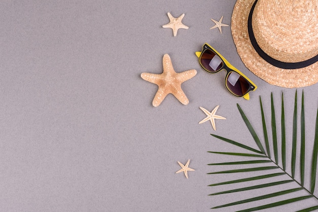 Óculos e chapéu com conchas e estrelas do mar em uma superfície colorida