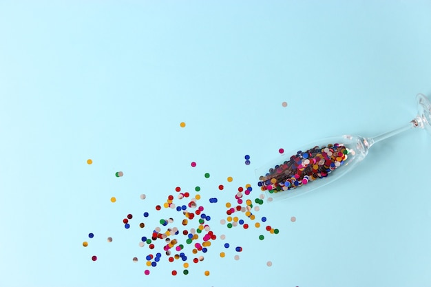Óculos e confetes em uma vista superior de fundo colorido