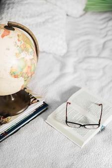 Óculos e globo perto de livros