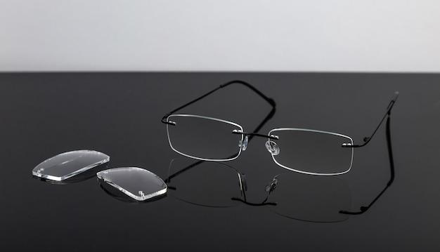 Óculos e lentes em uma mesa espelhada, em uma parede preta. conceito de visão.