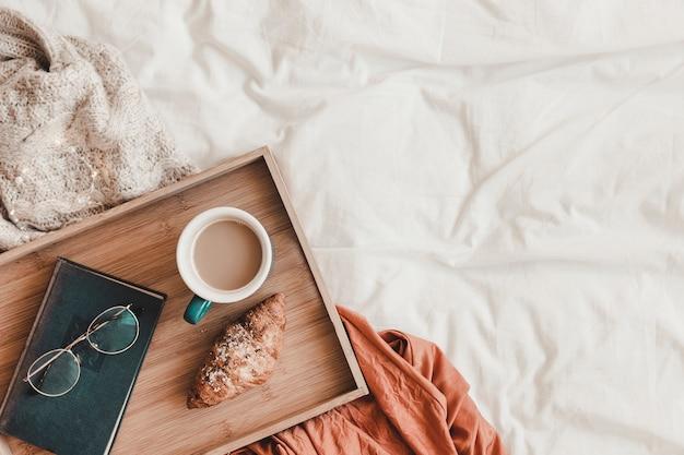 Óculos e livro perto de comida de café da manhã na cama