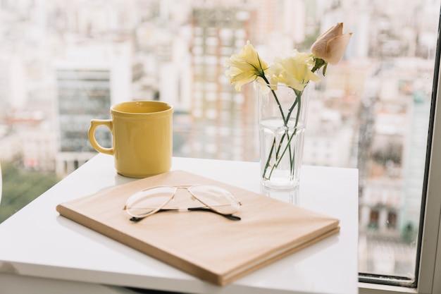 Óculos e livro perto de flores e caneca na mesa