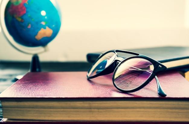 Óculos e livros ao lado da janela