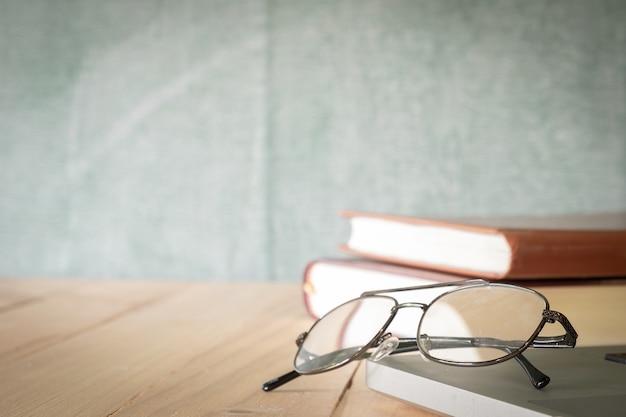 Óculos e livros sobre fundo de quadro de giz