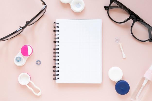 Óculos e objetos ópticos com maquete de notebook