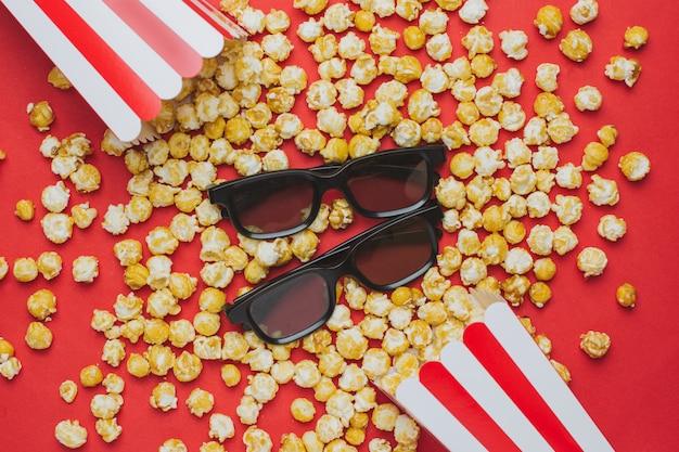 Óculos e pipoca na vista superior vermelha