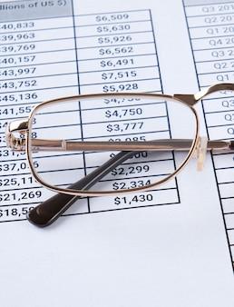 Óculos e relatórios financeiros no desktop