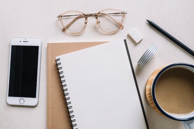 Óculos e smartphone perto de caderno e café