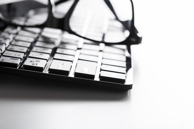 Óculos e teclado na mesa