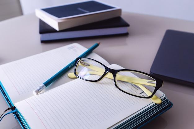 Óculos e um lápis estão no caderno. educação. o negócio.