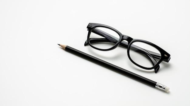 Óculos e um lápis no fundo branco