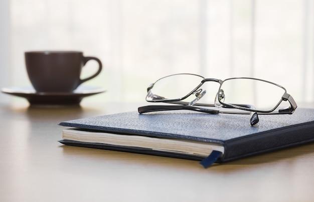 Óculos e um livro na mesa