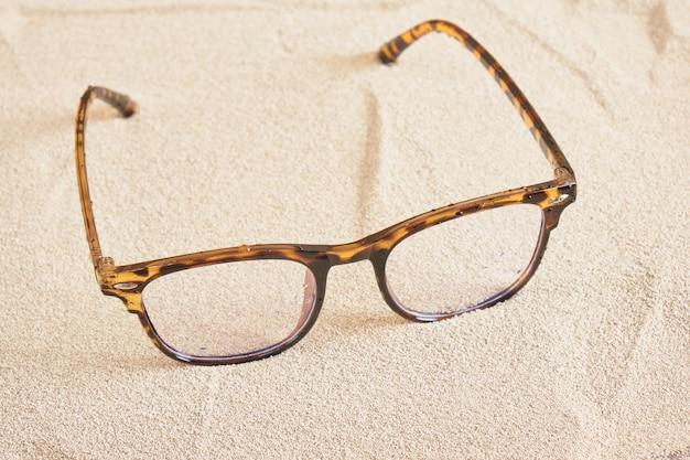 Óculos elegantes com armações de plástico pontilhadas na areia, vista superior do copy space