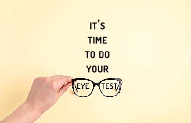 Óculos elegantes com texto desfocado é hora de fazer seu teste de visão. loja de ótica, seleção de óculos, exame de vista, exame de visão no oculista, conceito de acessórios de moda. vista superior, configuração plana