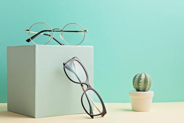 Óculos elegantes sobre parede pastel. loja de ótica, seleção de óculos, exame de vista, exame de visão no oculista, conceito de acessórios de moda. vista frontal