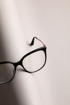Óculos elegantes sobre parede pastel. loja de ótica, seleção de óculos, teste de visão, exame de visão no oculista, conceito de acessórios de moda