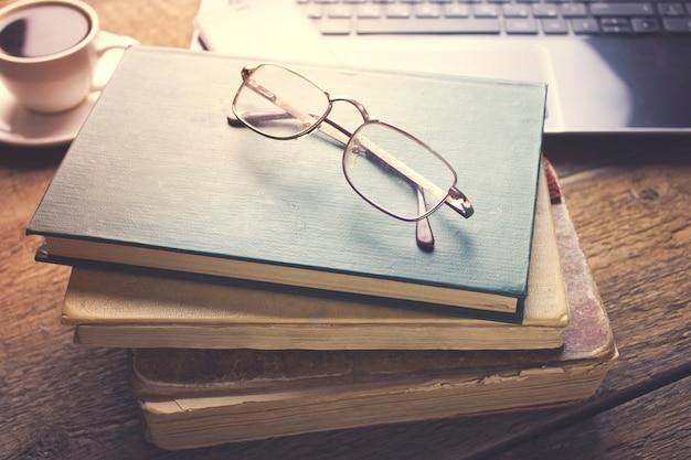 Óculos em livros, xícara de café e computador na mesa de madeira