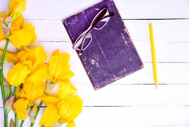 Óculos em um livro, ao lado de um buquê de íris amarelas