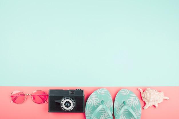 Oculos escuros; câmera; sandálias de dedo; concha em fundo coral e menta