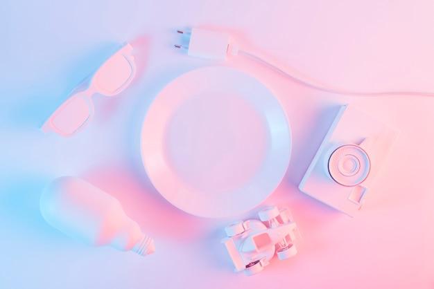 Oculos escuros; lâmpada; carro de fórmula um; plugue elétrico e câmera em fundo rosa e azul