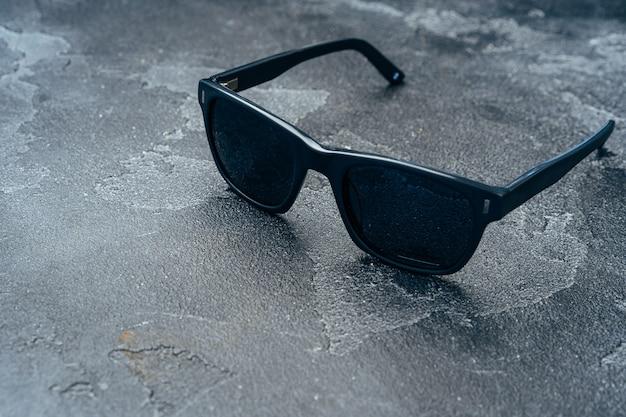 Óculos escuros masculinos na superfície cinza do concreto