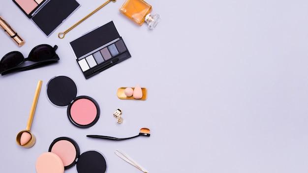 Oculos escuros; paleta de sombras; liquidificador; pinças; clutcher; frasco de perfume; pincéis de maquiagem e pó facial compacto no fundo roxo