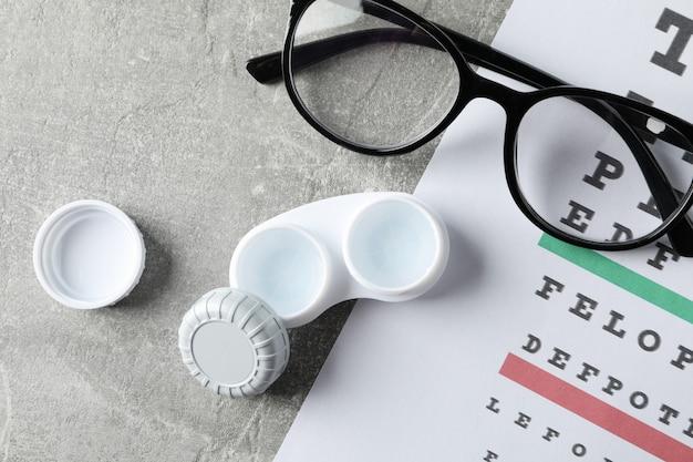 Óculos, estojo para lentes de contato e gráfico de teste de olhos na superfície cinza, vista superior