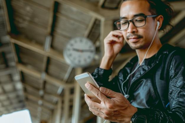 Óculos, homem asiático, ouvindo música do seu celular na estação de trem vintage.