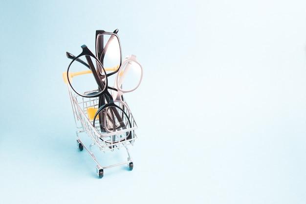 Óculos infantis e dois pares de óculos pretos para adultos em um pequeno carrinho de compras