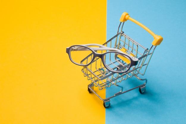 Óculos infantis para crianças pequenas em uma moldura de plástico cinza em um pequeno carrinho de compras em uma superfície colorida