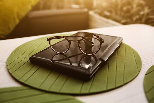 Óculos modernos de empresária, deitado no caderno na mesa de café. freelancer trabalhando no restaurante.