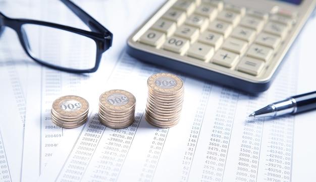 Óculos, moedas, calculadora, caneta em documentos financeiros. o negócio. finança