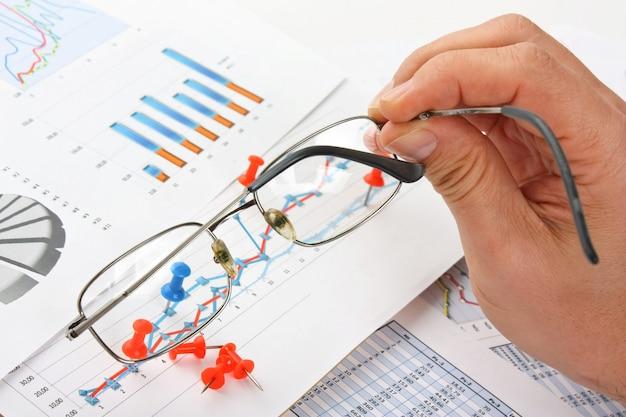 Óculos na mão e papel de trabalho