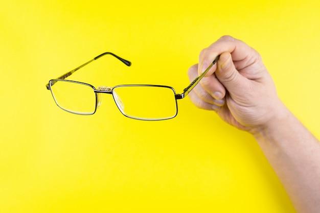 Óculos na mão