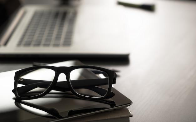 Óculos na mesa de escritório com computador notebook