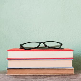 Óculos na pilha de livros