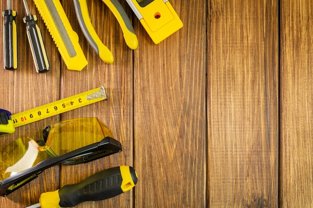 Óculos, nível de construção e roleta na placa de madeira
